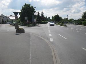 In der Mitte der Reilinger Straße sieht man die Querungshilfe. Wegen der Ampel an der Kreuzung ist hier leider keine Fußgängerampel möglich.